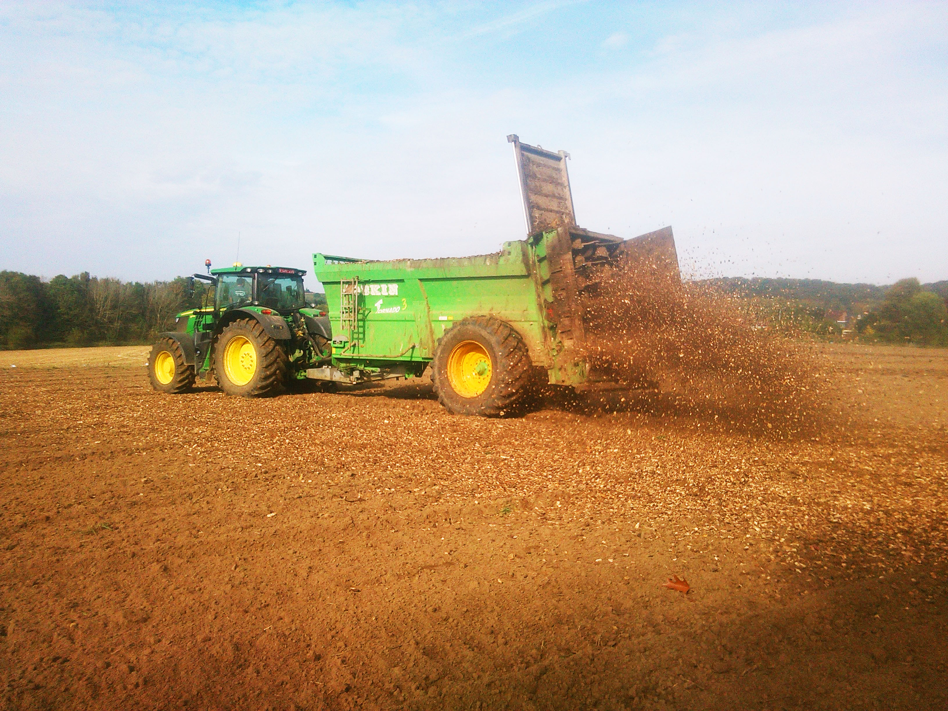 Woodchip being spread over the field by tractor. Photo credit: BDB